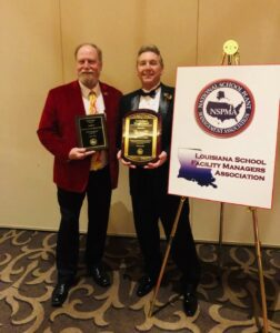 two adult older men, each holding a plaque-award.